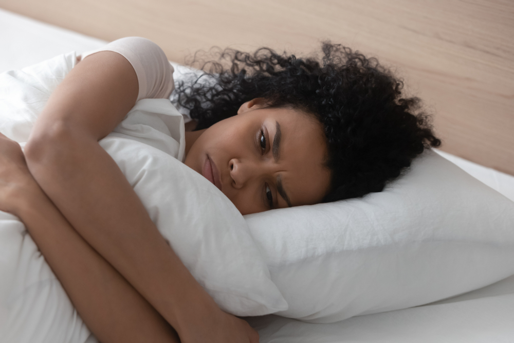 woman laying in bed looking sad